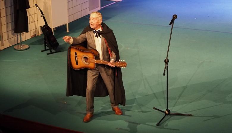Aktor Aleksander Pestyk stoi z gitarą na scenie Teatru Polskiego