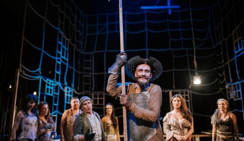 Na zdjęciu, na scenie stoi wysoki mężczyzna z długimi wąsami, który trzyma halabardę. Za nim, w głębi sceny stoi kilka osób, kobiet i mężczyzn ubranych w łachmany.