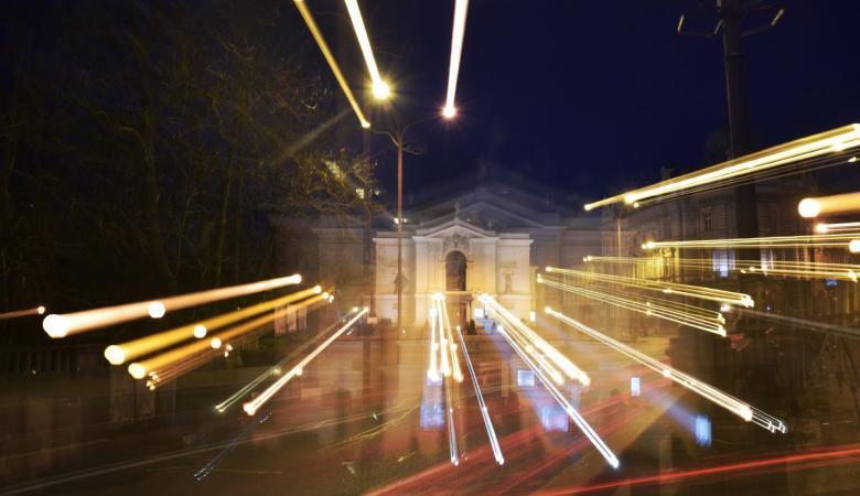 Budynek teatru sfotografowany nocą, rozświetlony smugami świateł miejskich latarni.