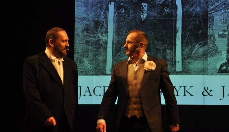 Dwóch mężczyzn w dziewiętnastowiecznych kostiumach stoi na scenie, tle czarno-białej grafiki