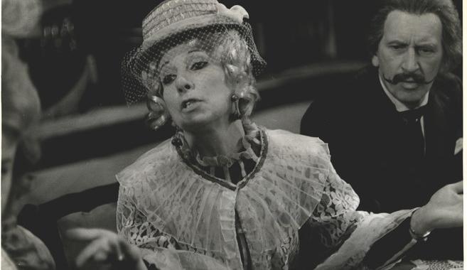 czarno-biała fotografia Anny Sobolewskiej w stylowym kapeluszu z mały rondem i woalką oraz koronkowym kołnierzu. Jest ona młodą blondynką o kręconych włosach sięgających za uszy. Za nią starszy, wąsaty mężczyzna.
