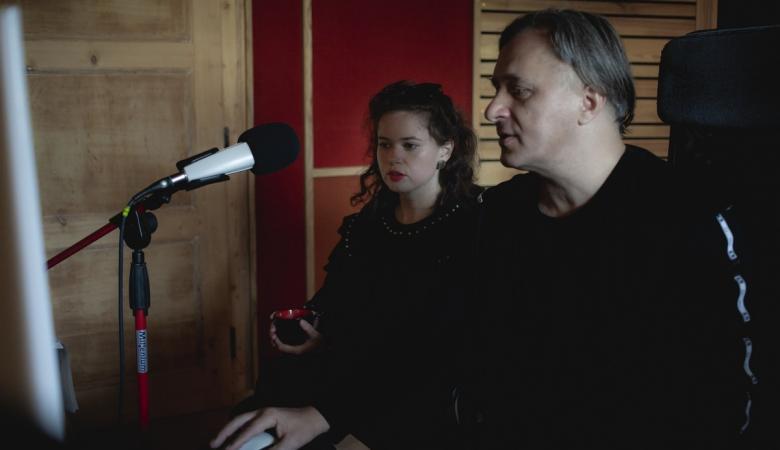 Młoda brunetka i około 45-letni mężczyzna o lekko siwiejących włosach siedzą w studio nagraniowym, przy mikrofonie. Oboje ubrani na czarno, skupieni na pracy.