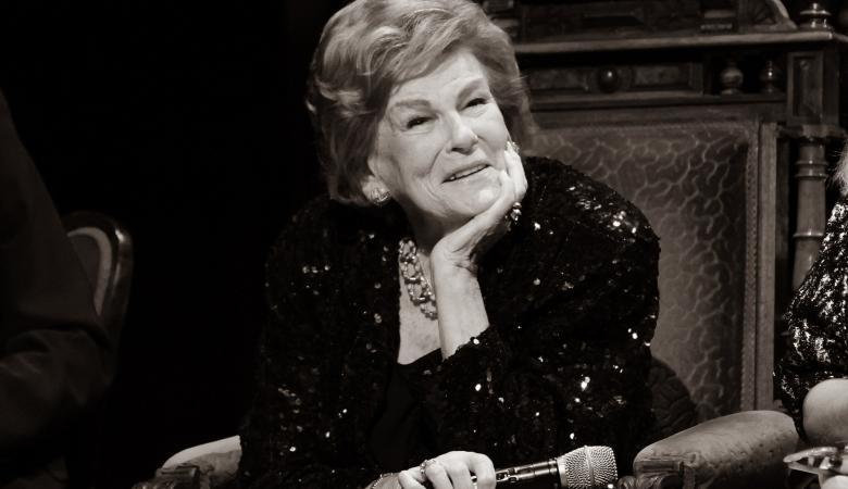 Czarno-biała fotografia starszej kobiety, ubranej elegancko, która siedzi na dużym, rzeźbionym fotelu.