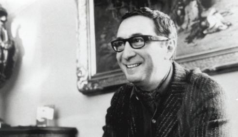 czarno-białe zdjęcie, na nim uśmiechnięty Leopold Tyrmand. Siedzi. Ma ciemne, krótkie włosy, okulary w czarnej oprawie i ciemną, prążkowaną marynarkę i koszulę z rozpiętym kołnierzykiem.