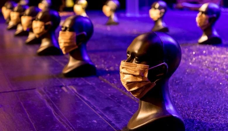 Na zdjęciu fragment sceny teatralnej. na niej ustawiono dwa rzędy głów manekinów w maseczkach chirurgicznych zasłaniających twarze.