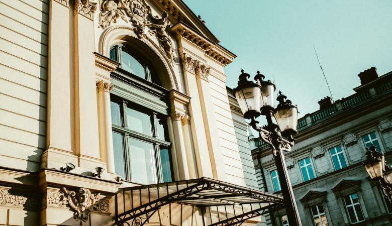 Fragment fasady zabytkowego budynku Teatru Polskiego, z dużym, półokrągłym oknem nad wejściem głównym.