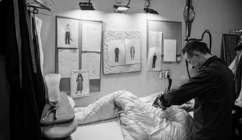 Na czarno-białym zdjęciu pracownia krawiecka. Na ścianie wisi kilka projektów kostiumów, nad nimi zapalone reflektorki. Przy dużym stole stoi brunet. Pochyla się nad szyciem.